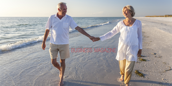 Happy senior man and woman couple walking and holding hands on a deserted tropical beach with bright clear blue sky